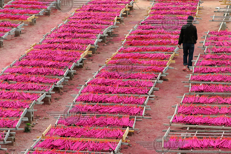 A worker walks past racks of incense laid out to dry at the Meizhengxiang Incense Factory. As religous life again becomes an important part of Chinese society, businesses related to Buddhism and Daoism have flourished. The factory has seen its sales quadruple since its establishment in 1996, reaching  5 million euros in 2003. The factory now employs over 200 workers, mostly migrants from other parts of China.