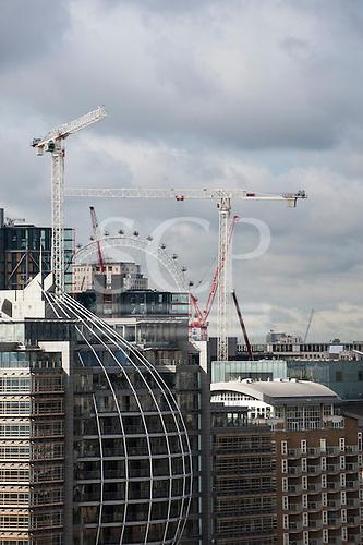 Southwark, London, England. Riverside House, Southwark Bridge Road with the London Eye framed by construction site cranes.