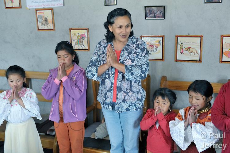 Sara Flores, a United Methodist missionary, prays with children who live on the contested Hacienda El Prado, near Cayambe, Ecuador. Flores is from Bolivia.