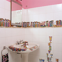 A quirky 1950's Fornasetti bathroom featuring wall tiles depicting a bookshelf and stacked cups as well as a painted basin
