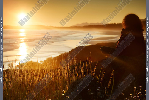 Woman watching a beautiful sunset on a shore of Pacific Rim National Park while the glowing sun is setting behind the Pacific ocean. Tofino, Vancouver Island, BC, Canada. Image © MaximImages, License at https://www.maximimages.com