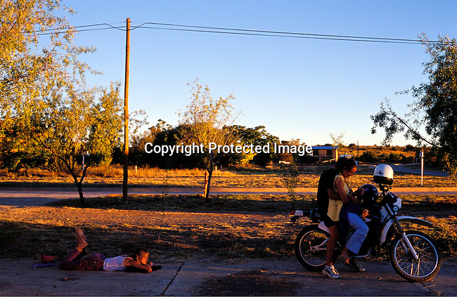 DIPOAFR00054.Culture Afrikaners Youths playing with a mobile phone on a motorbike in Orania, an all white community in Norhtern Cape, South Africa ..Photo: Per-Anders Pettersson/ iAfrika Photos