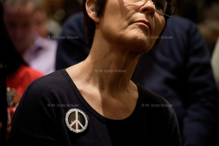 "A woman wearing a button with a peace sign that says ""Ron Paul for Peace"" listens as congressman Ron Paul speaks at a town hall meeting and rally at the Church Landing at Mills Falls hotel in Meredith, New Hampshire, on Jan. 8, 2012. Paul is seeking the 2012 Republican presidential nomination."