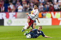 Juninho (8) of the New York Red Bulls is tackled by Chance Myers (7) of Sporting Kansas City. Sporting Kansas City defeated the New York Red Bulls 1-0 during a Major League Soccer (MLS) match at Red Bull Arena in Harrison, NJ, on April 17, 2013.