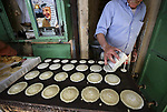 """A picture taken on May 16, 2018 shows a Palestinian vendor prepares """"Qatayef"""", traditional pancakes that are popular at a market during the holy month of Ramadan, in the West Bank city of Nablus. Ramadan is sacred to Muslims because it is during that month that tradition says the Koran was revealed to the Prophet Mohammed. The fast is one of the five main religious obligations under Islam. Muslims around the world will mark the month, during which believers abstain from eating, drinking, smoking and having sex from dawn until sunset. Photo by Ayman Ameen"""