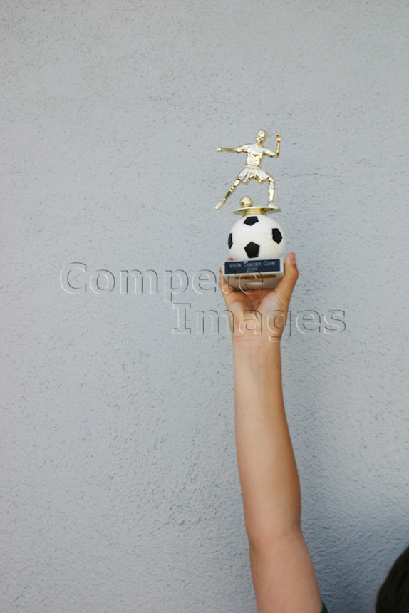 Young footballer holds trophy aloft after wininng final