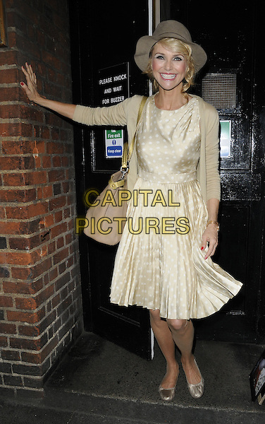 "CHRISTIE  BRINKLEY  .Departed after the evening performance  of ""Chicago"" at the Cambridge Theatre, London, England..July 14th, 2011.full length white cream beige dress cardigan polka dot pleats pleated bag purse gold hat smiling arm leaning.CAP/CAN.©Can Nguyen/Capital Pictures."
