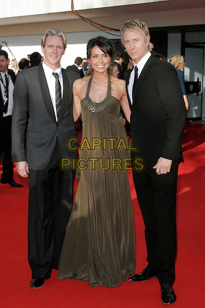 CHRISTINE BLEAKLEY & GUESTS.Arrivals at the British Academy Television Awards 2009, Royal Festival Hall, London, England. .April 26th 2009 .TV Baftas bafta's full length long maxi green khaki dress halterneck beige clutch bag black suit .CAP/AH.©Adam Houghton/Capital Pictures..