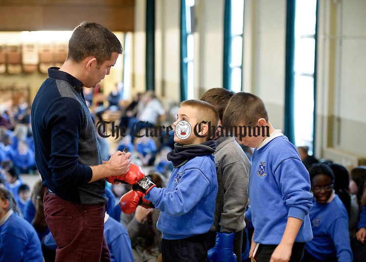 Former WBA Super bantamweight champion Bernard Dunne, a Carambola Kids ambassador,  signing a boxing glove for pupil Rhys Donovan during his visit to The Holy family school in Ennis to promote the importance of healthy eating and physical fitness. Photograph by John Kelly.