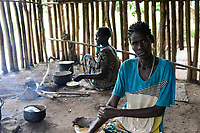 ETHIOPIA, Gambela, Anuak tribe, woman cooking in kitchen, she fled from the civil war in South Sudan / AETHIOPIEN, Gambela, Dorf GOG DIPACH der Ethnie ANUAK, Frau Achala Gora (Name geaendert) ist vor dem Buergerkrieg aus dem Suedsudan mit ihren Kindern geflohen und fand Aufnahme im Dorf mit Hilfe von Verwandten und Nachbarn, kocht in ihrer Kueche