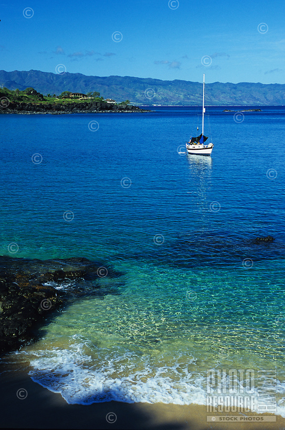 Sailboat on the placid summer waters at Waimea Bay on the north shore of Oahu