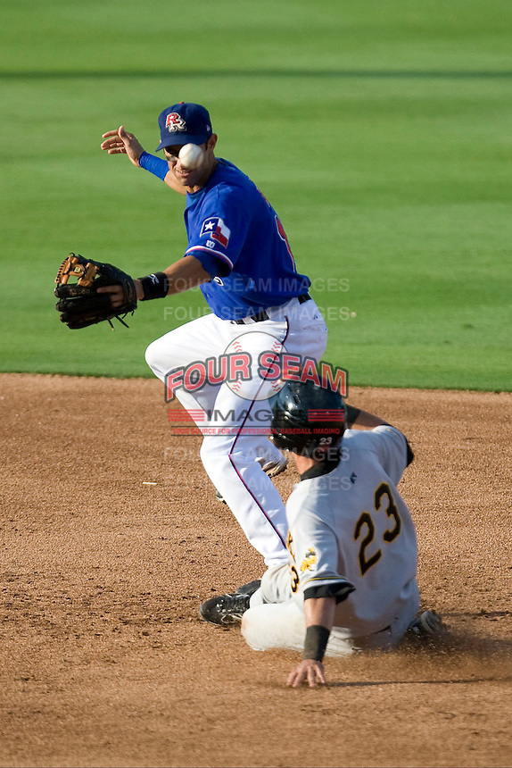 Round Rock Express second baseman Matt Kata #15 misses the throw as baserunner Gil Velazquez #23 slides into second base during a Pacific Coast League game against the Salt Lake Bees at The Dell Diamond in Round Rock, Texas on August 6, 2011. Round Rock defeated Salt Lake 3-1.  (Andrew Woolley/Four Seam Images)