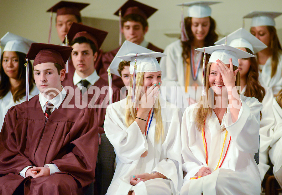 Graduates Jaida Bartholomew (C) and Shelby Christine Codd (R) share a laugh onstage during commencement ceremonies at Faith Christian Academy Friday May 29, 2015 in Sellersville, Pennsylvania. On far left is Dylan Connor Brown. (Photo by William Thomas Cain/Cain Images)