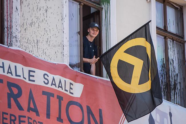 """Am Samstag den 20 Juli 2019 versuchten in Halle an der Saale ca. 200 Mitglieder und Anhaenger der rechtsextremen """"Identitaeren Bewegung"""", IB, eine Demonstration durchzufuehren. Sie versammelten sich dafuer vor dem Haus der IB in der Adam-Kuckhoff-Straße 16. Aufgrund von Gegenprotesten konnten die Rechtsextremen jedoch nicht marschieren, da alle Straßen um ihr Haus von Gegendemonstranten blockiert wurden.<br /> Im Bild: Ein Mitglied der """"Identitaeren"""" mit Fahne am Fenster des IB-Haus.<br /> 20.7.2019, Berlin<br /> Copyright: Christian-Ditsch.de<br /> [Inhaltsveraendernde Manipulation des Fotos nur nach ausdruecklicher Genehmigung des Fotografen. Vereinbarungen ueber Abtretung von Persoenlichkeitsrechten/Model Release der abgebildeten Person/Personen liegen nicht vor. NO MODEL RELEASE! Nur fuer Redaktionelle Zwecke. Don't publish without copyright Christian-Ditsch.de, Veroeffentlichung nur mit Fotografennennung, sowie gegen Honorar, MwSt. und Beleg. Konto: I N G - D i B a, IBAN DE58500105175400192269, BIC INGDDEFFXXX, Kontakt: post@christian-ditsch.de<br /> Bei der Bearbeitung der Dateiinformationen darf die Urheberkennzeichnung in den EXIF- und  IPTC-Daten nicht entfernt werden, diese sind in digitalen Medien nach §95c UrhG rechtlich geschuetzt. Der Urhebervermerk wird gemaess §13 UrhG verlangt.]"""
