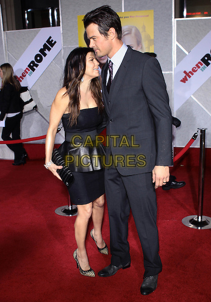 """FERGIE (STACY FERGUSON) & JOSH DUHAMEL .Attending the Los Angeles Premiere of """"When In Rome"""" held at The El Capitan Theater, Hollywood, CA, USA, .27th January 2010..arrivals full length leather peplum dress strapless black cream striped shoe clutch bag profile leaning in close suit tie married couple husband wife grey gray .CAP/ADM/TC.©T. Conrad/AdMedia/Capital Pictures."""