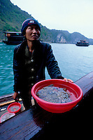 Woman with plastic bowl of fresh crabs for sale, Halong Bay, Vietnam