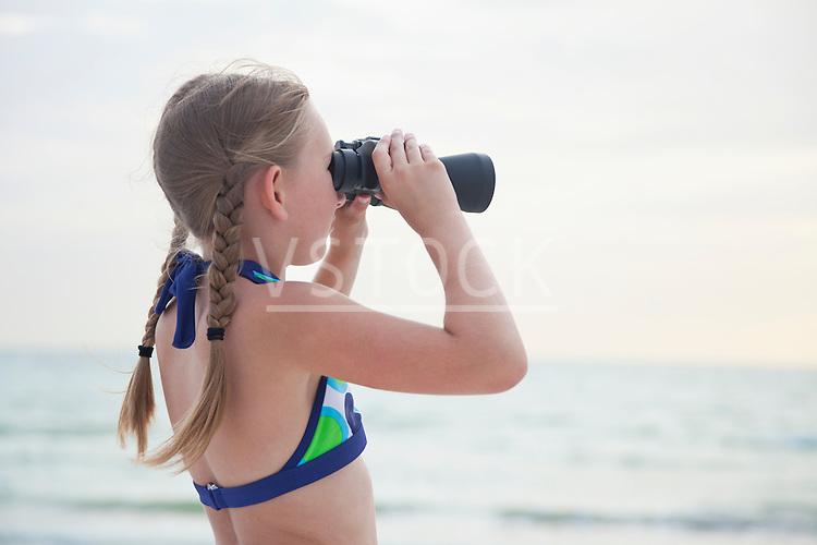 USA, Florida, St. Pete Beach, Girl (8-9) looking through binoculars on beach