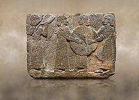 Photo of Hittite monumental relief sculpted orthostat stone panel of Procession. Basalt, Karkamıs, (Kargamıs), Carchemish (Karkemish), 900 - 700 B.C. Goddess Kubaba. Anatolian Civilisations Museum, Ankara, Turkey.<br /> <br /> Procession for. There are four figures on the other face of the orthostat. The leftmost figure plays a pipe, while the other three figures play the drums. All of the figures have long skirts and same body heights.  <br /> <br /> Against a brown art background.