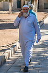 A Muslim man wearing the traditional thobe or thawb walks on the Temple Mount or al-Haram ash-Sharif in the Old City of Jerusalem while talking on his mobile phone.  The Old City of Jerusalem and its Walls is a UNESCO World Heritage Site.