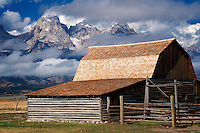 Barn at John Moulton Homestead with Teton Mountains and clearing clouds. Teton National Park, Wyoming