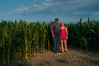 Ohio farmer Kevin Scott and his daughter, Karlee, pose at the edge of a corn field in afternoon sun.