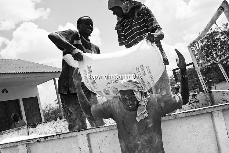 Workers take down food supplies at the reception centre in IFO-1camp in the Dadaab refugee camp in northeastern Kenya. Photo: Sanjit Das/Panos