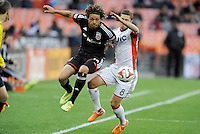 Washington, D.C.- March 29, 2014. Nick DeLeon (14) of D.C. United goes against Chris Tierney (8) of the New England Revolution.  D.C. United defeated the New England Revolution 2-0 during a Major League Soccer Match for the 2014 season at RFK Stadium.