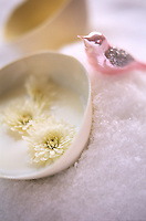 Flowers float in a bowl of yoghurt nestled in snow and watched over by a pink metallic bird