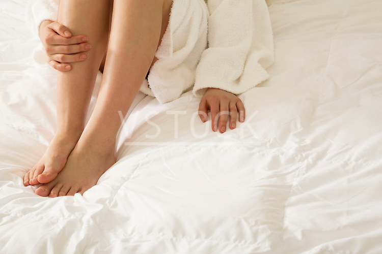 Low section of barefoot female wearing bathrobe, sitting on white bedding