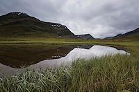 Reflection of mountain landscape of Tjäktjavagge valley in small pond near Sälka hut; Kungsleden trail; Lapland; Sweden
