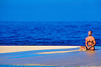 A man meditates in a yoga posture on a white sandbar with the beautiful, vivid, blue ocean in the background.