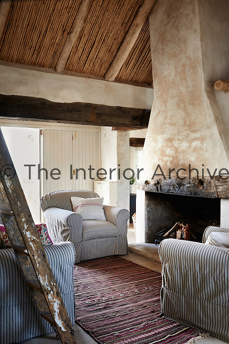 A country living room with a rustic ceiling and stone fireplace. The room is furnished with a three piece suite upholstered in grey and white striped fabric.
