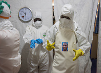 Health care workers don their PPE, complete with portraits, in the ELWA II ETU (Ebola treatment unit), Monrovia, Liberia on Wednesday, March 4, 2015. <br /> Occidental College professor Mary Beth Heffernan's PPE Portrait Project involves creating wearable portraits of the health care workers who must wear PPE (personal protective equipment) when working with patients.<br /> (Photo by Marc Campos, Occidental College Photographer) Mary Beth Heffernan, professor of art and art history at Occidental College, works in Monrovia the capital of Liberia, Africa in 2015. Professor Heffernan was there to work on her PPE (personal protective equipment) Portrait Project, which helps health care workers and patients fighting the Ebola virus disease in West Africa.<br />