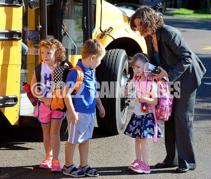 LOWER SOUTHAMPTON, PA - AUGUST 28:   Principal Michelle Burkholde (R) helps Lisa Kearns with her backpack after she got off of the bus as other students arrive on at the start of the first full day of school at Lower Southampton Elementary School August 28, 2014 in Lower Southampton, Pennsylvania. (Photo by William Thomas Cain/Cain Images)