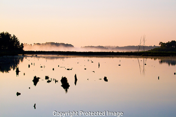 A foggy summer morning in Tomah, Wisconsin.  I was driving to a job at a plant, and noticed the mist rising about this small lake. My shoot at the plant was contingent upon sunny skies, so I knew I had time to pull over and snap a few landscape photos.