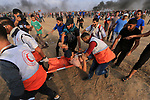 A wounded Palestinian protester is evacuated during clashes with Israeli troops in tents protest where Palestinians demand the right to return to their homeland at the Israel-Gaza border, in al-Bureij in the center of Gaza Strip on October 19, 2018. Photo by Mahmoud Khattab
