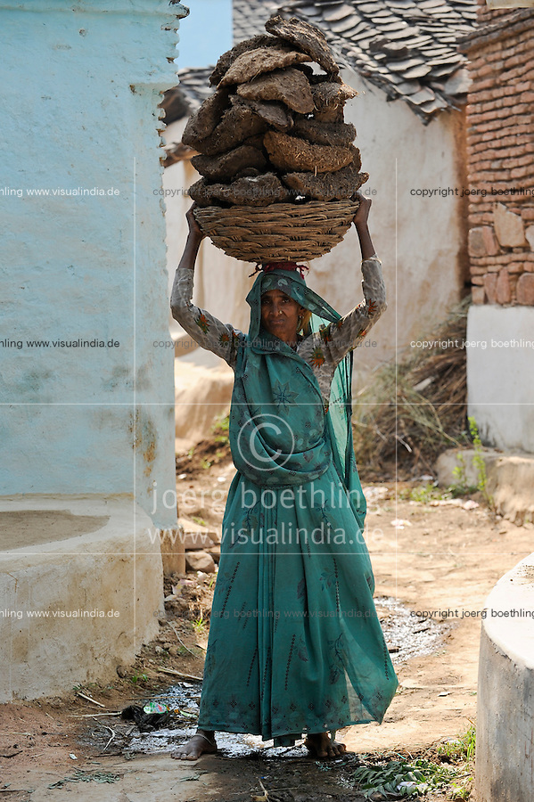 INDIA Uttar Pradesh , dalit women in village in Bundelkhand, woman carry cow dung on the head, the cow dung is used as cooking fuel  / INDIEN Uttar Pradesh, Frauen unterer Kasten und kastenlose Frauen, Dalits, in Doerfern in Bundelkhand, Frau traegt Kuhdung auf dem Kopf, die Kuhfladen werden als Brennstoff zum Heizen und Kochen verwendet