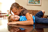 Dawn Berge cuddles with her autistic son Zachary age 5 as his sister Carson, age 7, watches at their home on Friday, July 30, 2010, in Crestview, Fla. The Berges have filed a lawsuit against the Department of Defense, which administers their family's insurance, a program for active and retired military families known as TRICARE. They hope to recover the nearly $56,000 in expenses they incurred for Zachary's ABA therapy which is teaching him to speak and has eased his tantrums because he didn't know how to express what he wanted to say.  (Colin Hackley/for the Chicago Tribune)    B58603799Z.1