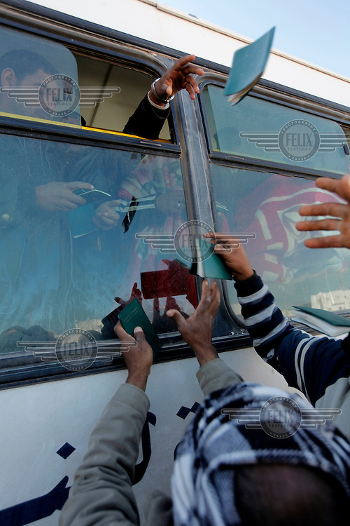 Passports gets thrown out of a bus window after a unsuccessful attempt to board a bus in an orderly manner.  Thousands of people, mainly Egyptian workers, fled unrest in Libya and cross the border into Tunisia. Some slept in the open for several days before being processed. .At the same time forces loyal to Col. Gaddafi fought opposition forces in various parts of the country.