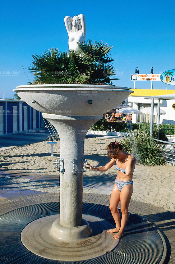 Italy. Province Emilia-Romagna. Rimini. A tourist woman takes a shower. Life in the summer on the sand beach. Rimini is located on the Adriatic Sea and is one of the most famous seaside resorts in Europe, thanks to its 15 km-long sandy beach. 17.07.99 © 1999 Didier Ruef  *** Local Caption *** .