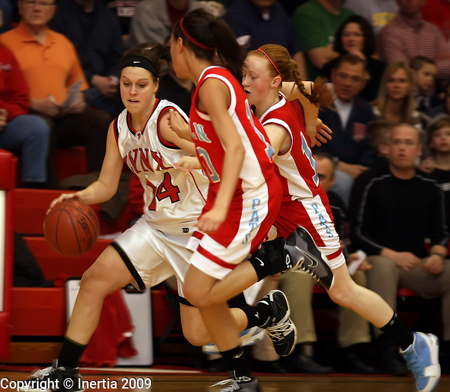 BRANDON, SD - MARCH 2:  Claire Choudek #24 of Brandon Valley looks to get around Caiti Slattery #12 and Shanice Henderson #10 of Lincoln in the first half of their game Monday night in the first round of their District 2AA game Monday night in Brandon. (Photo by Dave Eggen/Inertia)