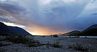 The sun sets through a rainstorm near midnight along the Canning River, in Alaska's Arctic National Wildlife Refuge.