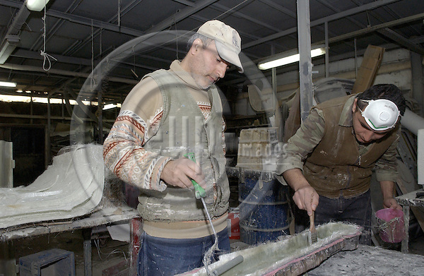 Istanbul-Turkey - 07 April 2006---Chemical workers in a small-scale industrial company, moulding a polyester component part under rather unhealthy condition; affiliated to Lastik-Is / ICEM (International Federation of Chemical, Energy, Mine and General Workers' Unions)---trade union-economy-industry-enterprise-labour-people---Photo: Horst Wagner/eup-images