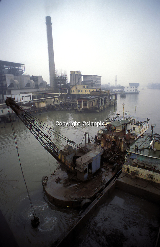 A barge and crane sit before the Shajiao power station at  the Pearl River in Guangzhou, China.