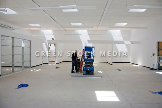 A worker in a energy efficient office. Natural sunlight from skylights fills the 'z squared' (zero energy/zero carbon emissions) office under construction. The floor has a radiant heat system. San Jose, California, USA