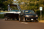 Black Chevrolet Avalanche towing boat