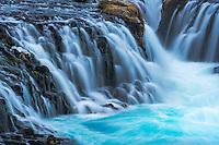 Turquoise water cascades over basalt columns of Bruarfoss falls.