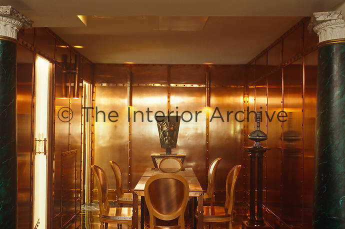 The walls and furniture in this extraordinary dining room are clad in copper