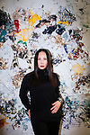 Eva Chow poses for a portrait in front of a painting done by her husband Michael in their home in Los Angeles, California October 19, 2015.