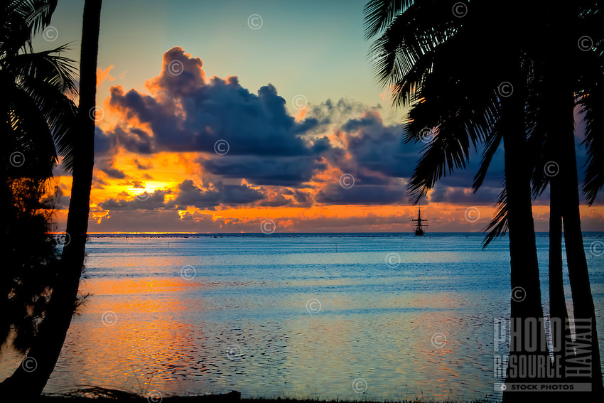 A silhouette of palm trees at sunset at Amuri Beach, with a Dawn Treader in the distance, Amuri Beach, Aitutaki Island, Cook Islands.